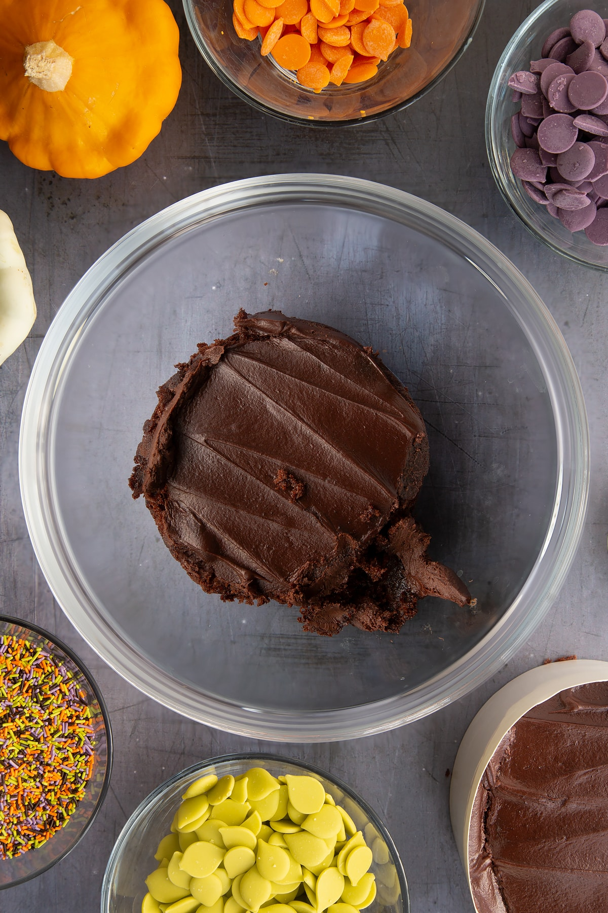 Chocolate fudge cake in a bowl. Ingredients to make Halloween cake pops surround the bowl.