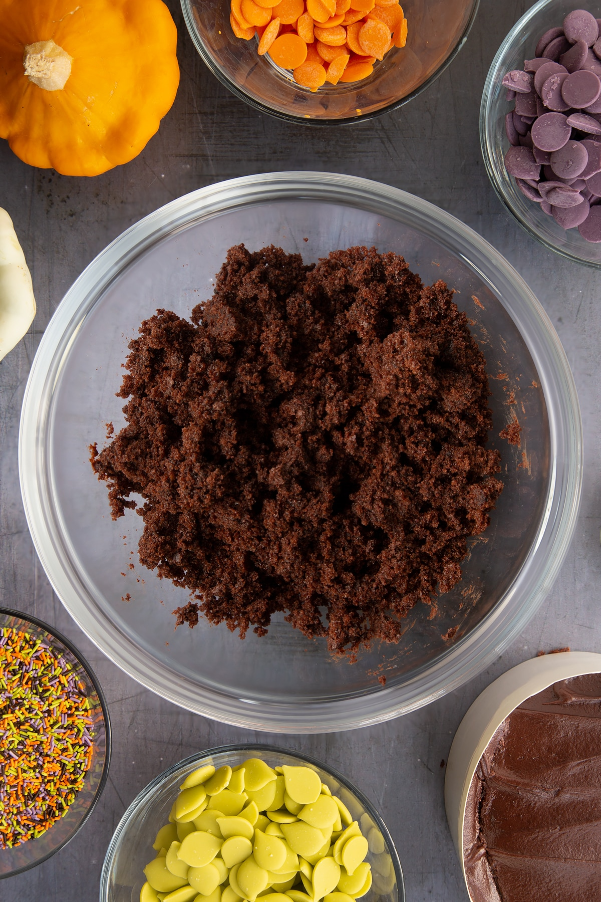Chocolate fudge cake broken down in a bowl. Ingredients to make Halloween cake pops surround the bowl.