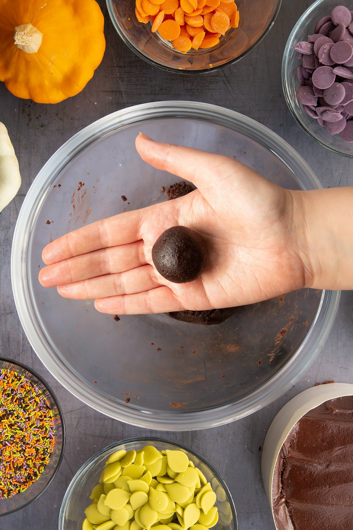 A hand holding a ball of chocolate cake. Ingredients to make Halloween cake pops surround the bowl beneath.