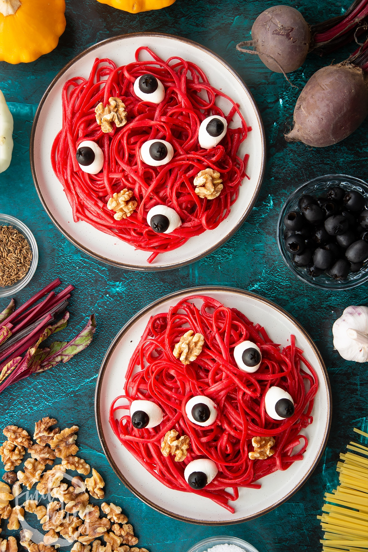 Two plates with a beetroot Halloween pasta recipe, topped with mozzarella eyes and walnut brains.