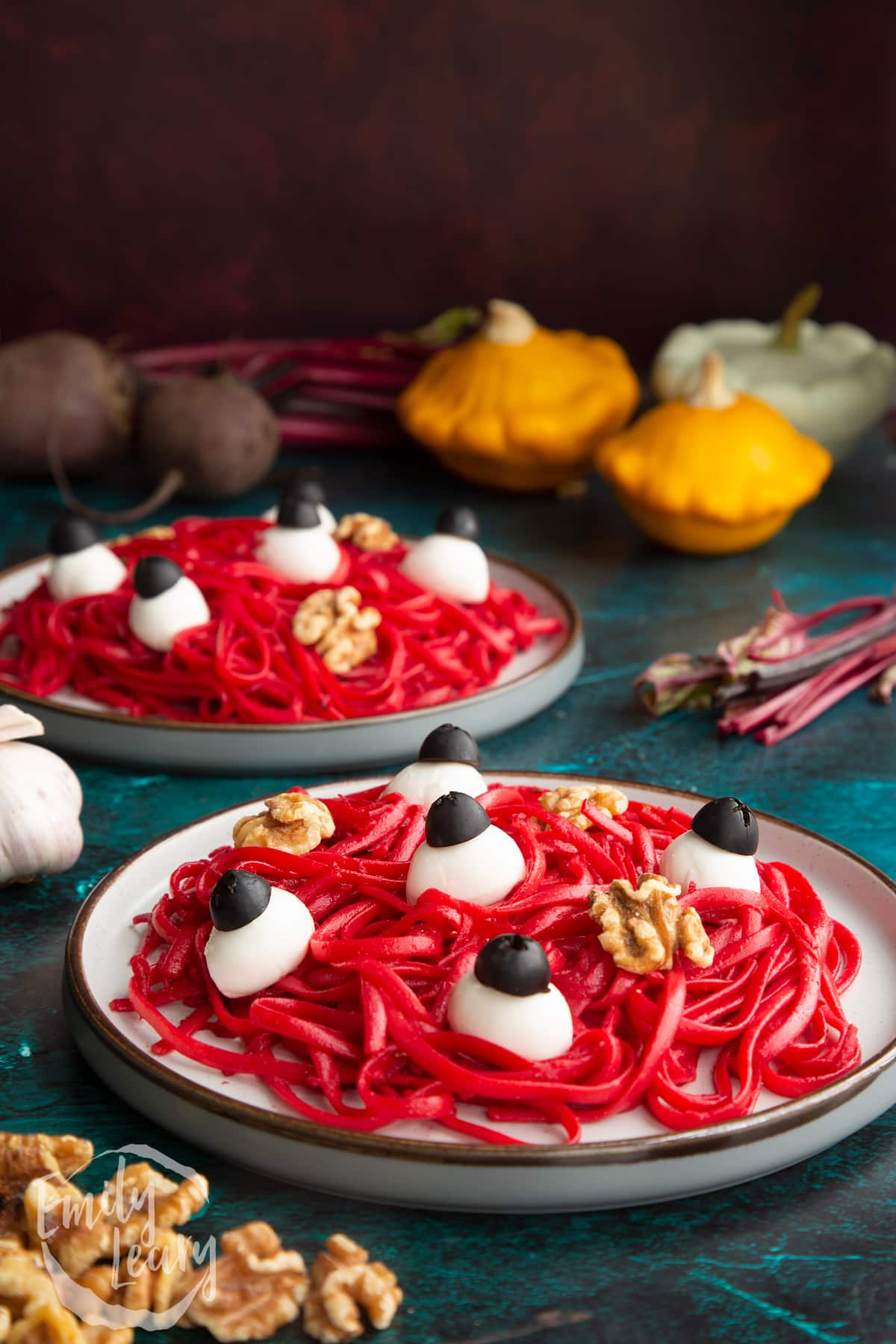 A plate with a beetroot Halloween pasta recipe, topped with mozzarella eyes and walnut brains.