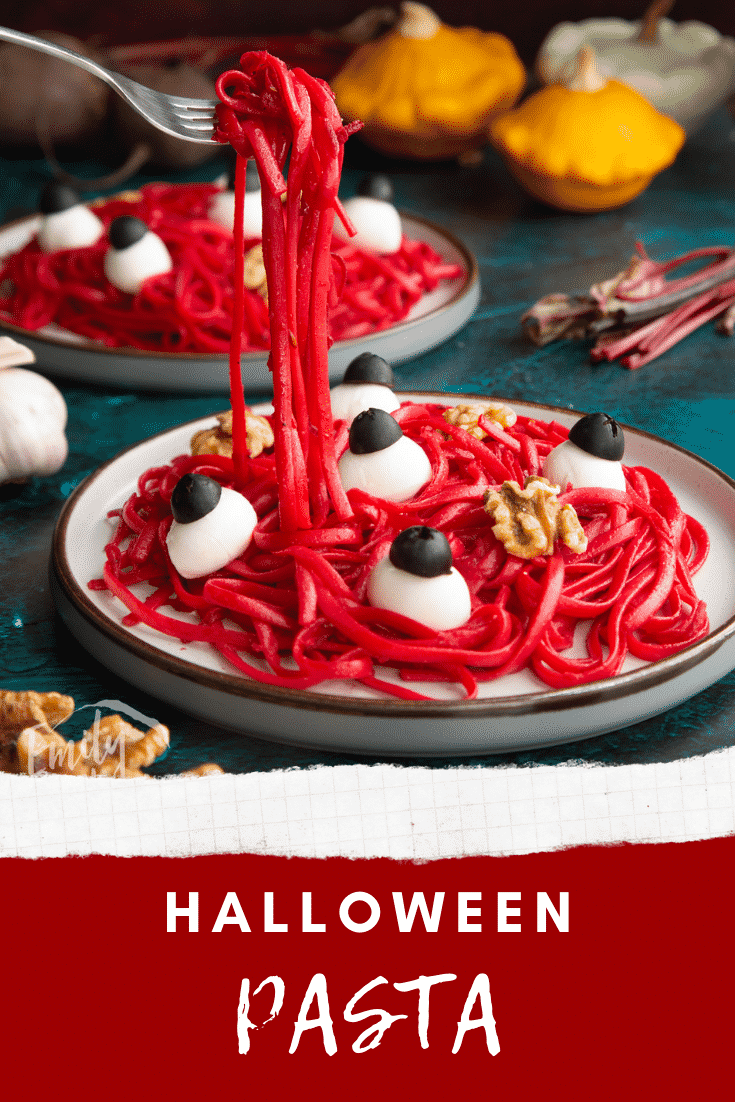 Two plates with a beetroot Halloween pasta recipe, topped with mozzarella eyes and walnut brains. A fork lifts some pasta. Caption reads: Halloween pasta.