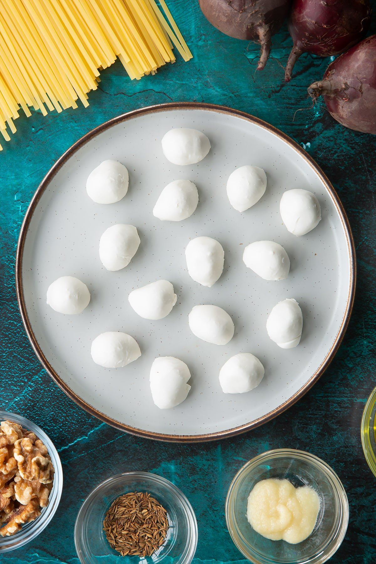 Mozzarella pearls on a plate. Ingredients to make a Halloween pasta recipe surround the plate.