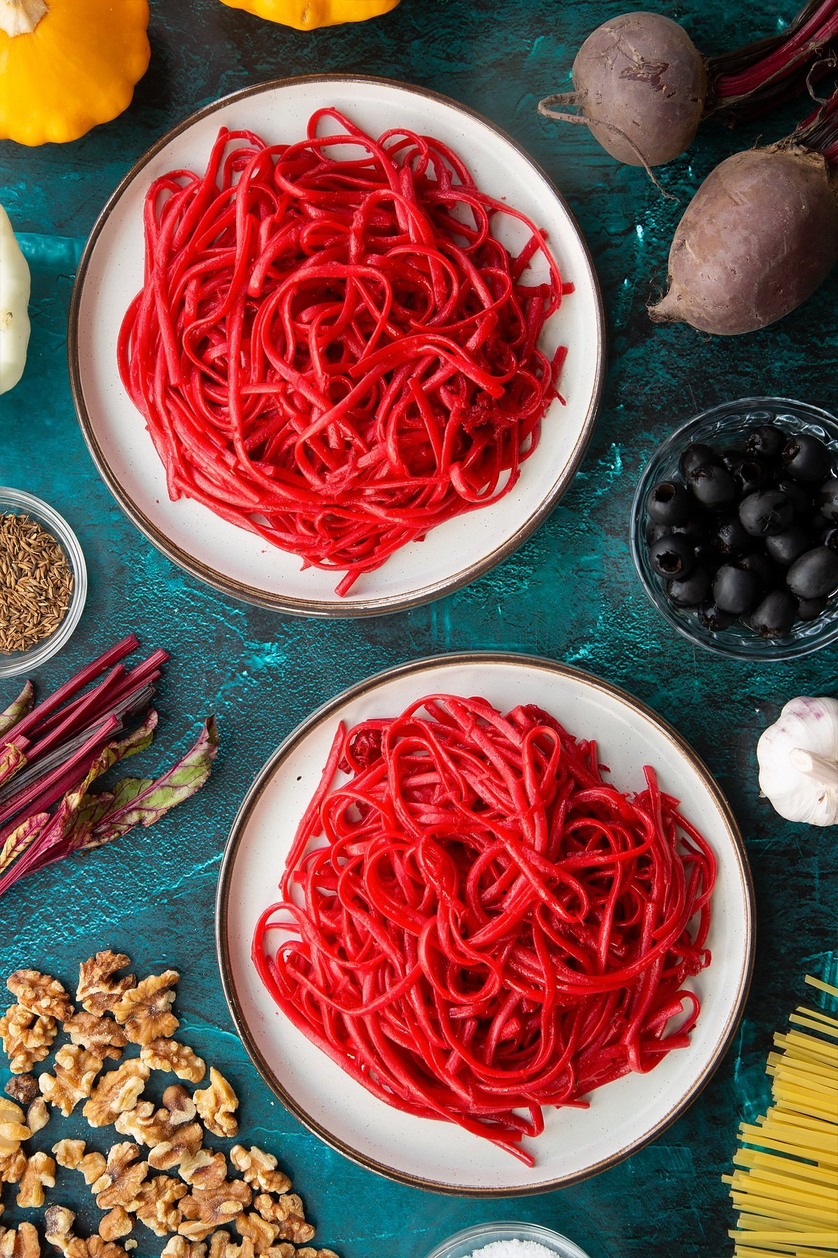 Two plates with beetroot pasta.