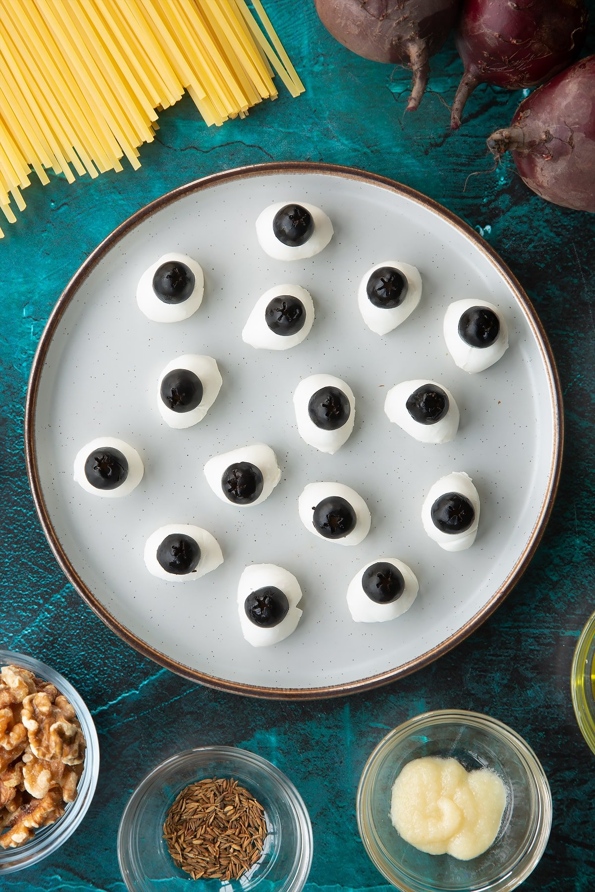 Mozzarella pearls topped with black olives on a plate. Ingredients to make a Halloween pasta recipe surround the plate.