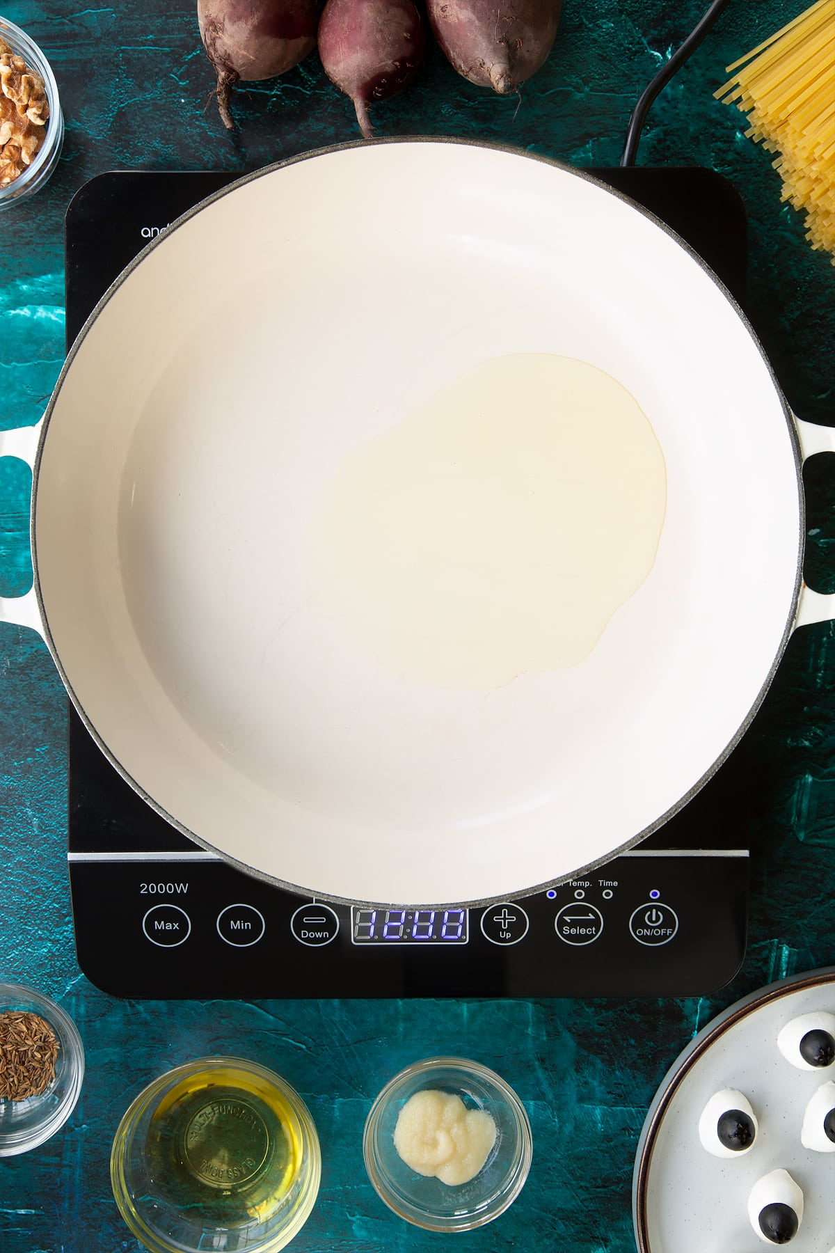 Oil in a pan. Ingredients to make a Halloween pasta recipe surround the pan.