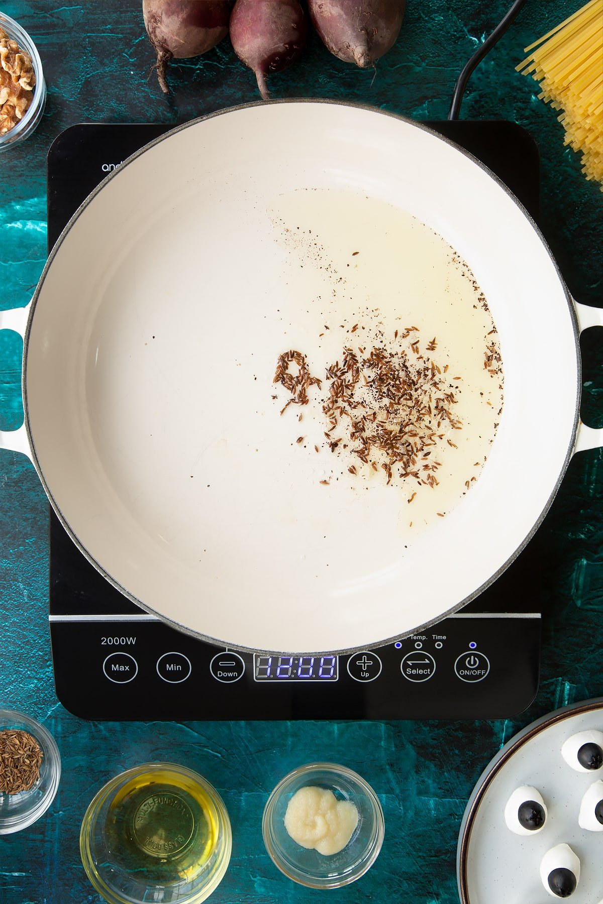 Fried cumin seeds in oil in a pan. Ingredients to make a Halloween pasta recipe surround the pan.