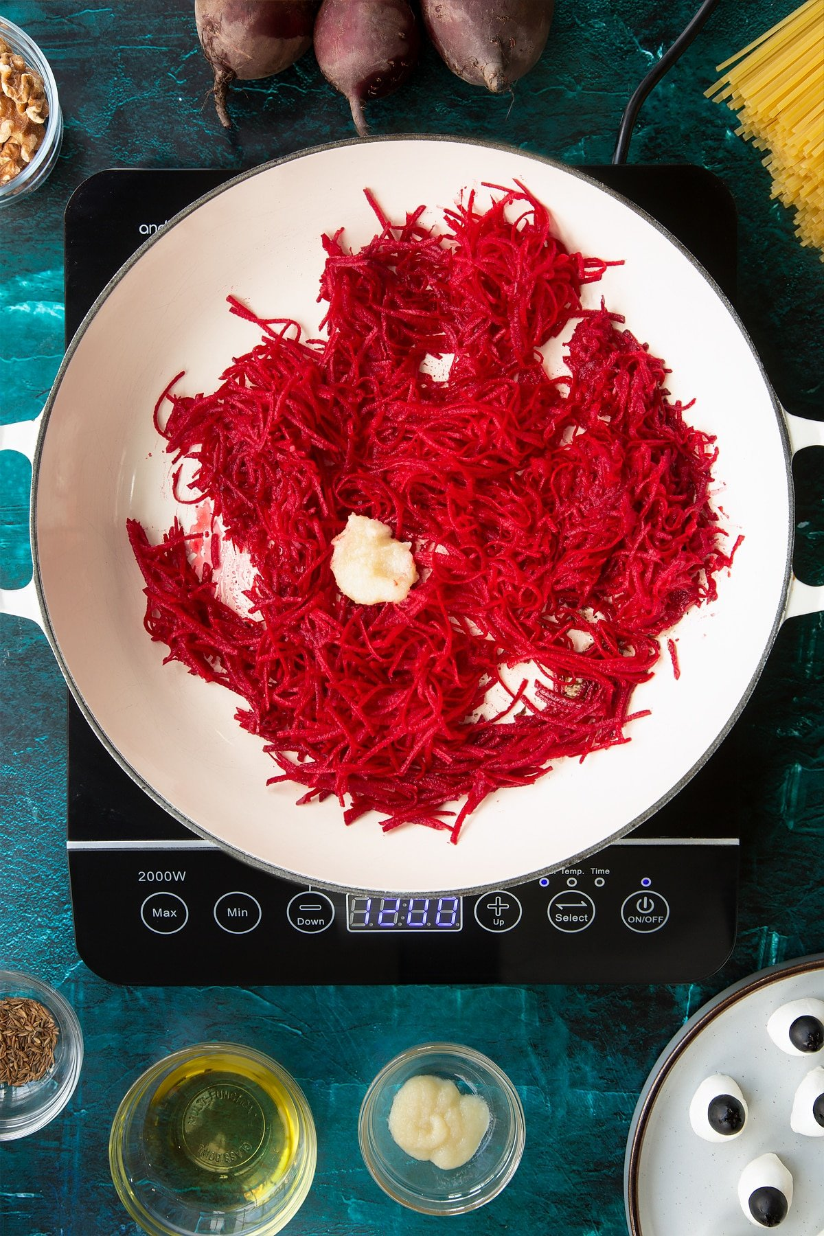 Grated beetroot and garlic in a pan. Ingredients to make a Halloween pasta recipe surround the pan.