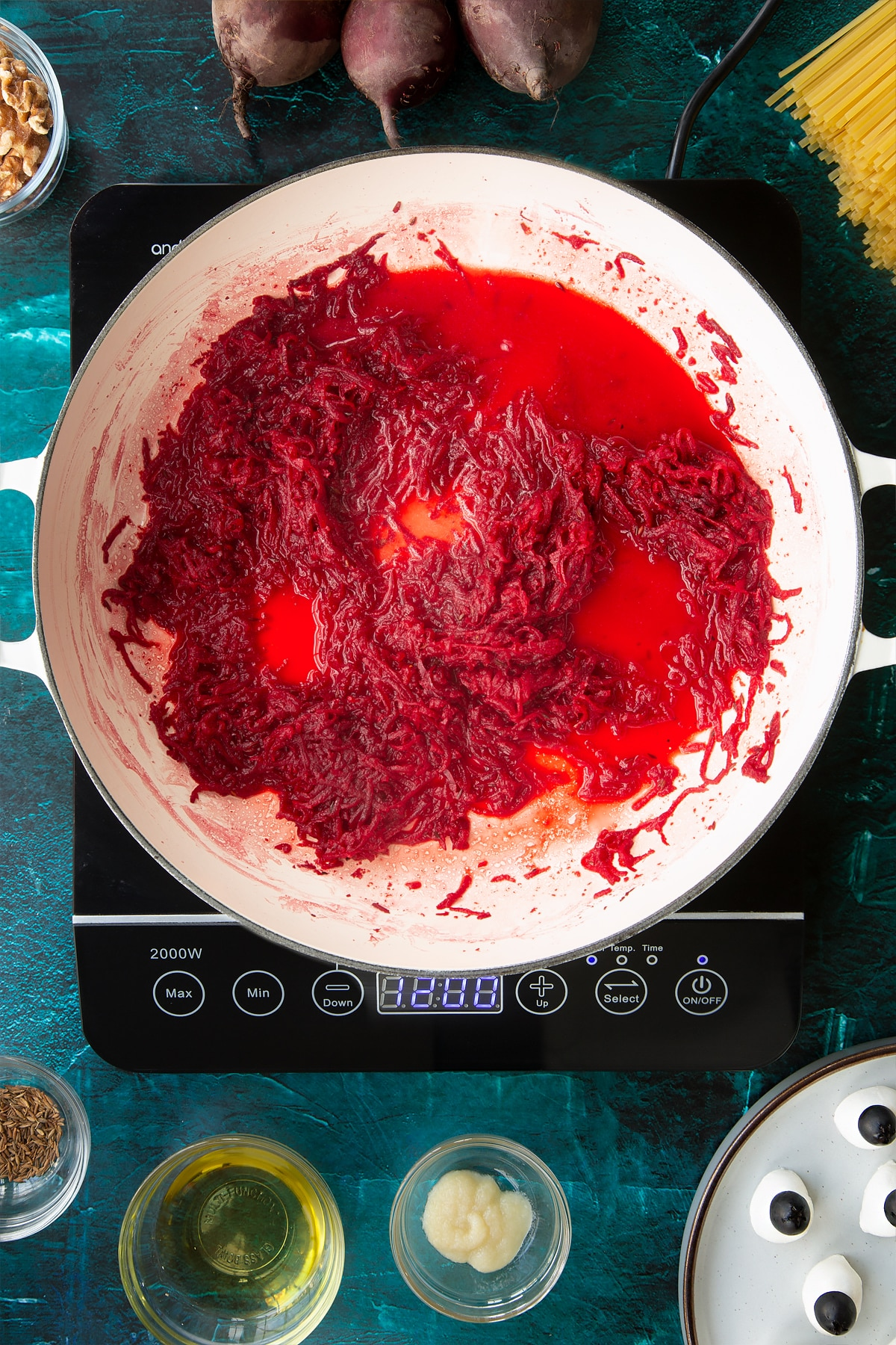 Sweated beetroot in a pan with added water. Ingredients to make a Halloween pasta recipe surround the pan.